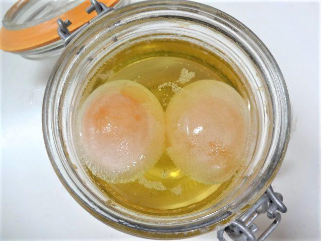広口のビンに酢と卵を入れ1日経ち、卵の殻が薄くなってきた写真(2日目)
